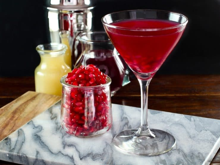 A bright red cocktail in a martin-style cocktail glass next to a small jar of pomegranate seeds