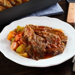 A slice of beef brisket next to a side of vegetables and topped with gravy on a round white plate.
