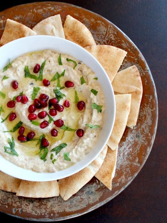 Vertical shot of Roasted Eggplant Yogurt Dip topped with pomegranate arils and fresh mint, on a platter with pieces of pita.