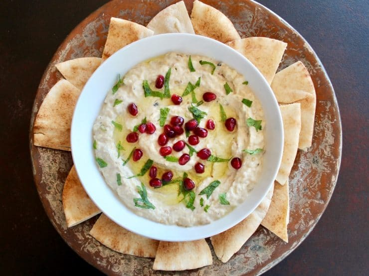 Horitzontal shot of Roasted Eggplant Yogurt Dip topped with pomegranate arils and fresh mint, on a platter with pieces of pita.