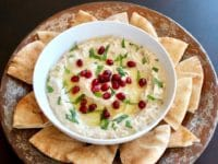 Overhead shot of Roasted Eggplant Yogurt Dip topped with pomegranate arils and fresh mint, on a platter with pieces of pita.