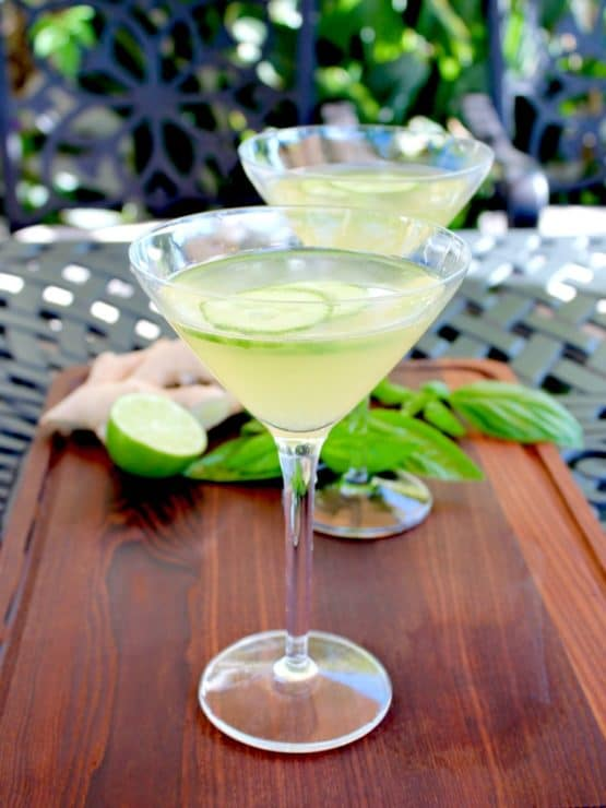 Two cucumber ginger martinis in martini glasses on wooden cutting board garnished with cucumber slices, basil, lime and whole ginger root in background, on outdoor black table. Vertical shot.