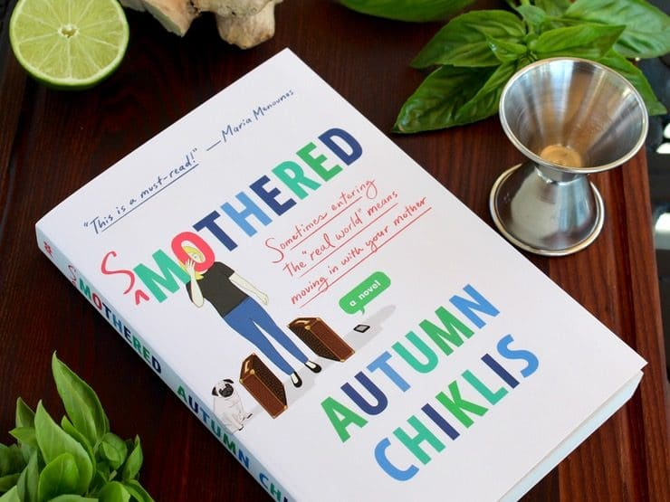 Book - Smothered by Autumn Chills on wooden cutting board with fresh basil, metal jigger, half lime and whole ginger root.