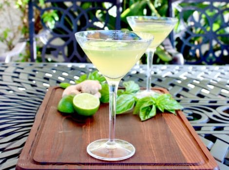 Two cucumber ginger martinis in martini glasses on wooden cutting board garnished with cucumber slices, basil, lime and whole ginger root in background, on outdoor black table. Horizontal shot.