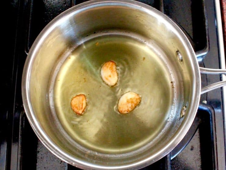 Three cloves of pan-roasted garlic, golden brown, in olive oil in saucepan.