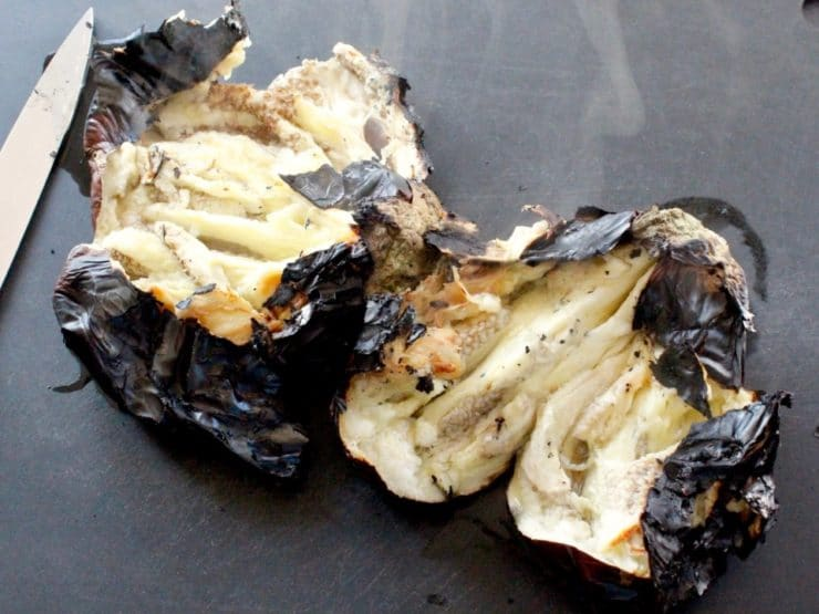 Flame roasted eggplant on cutting board, cut open, revealing steaming eggplant flesh inside.