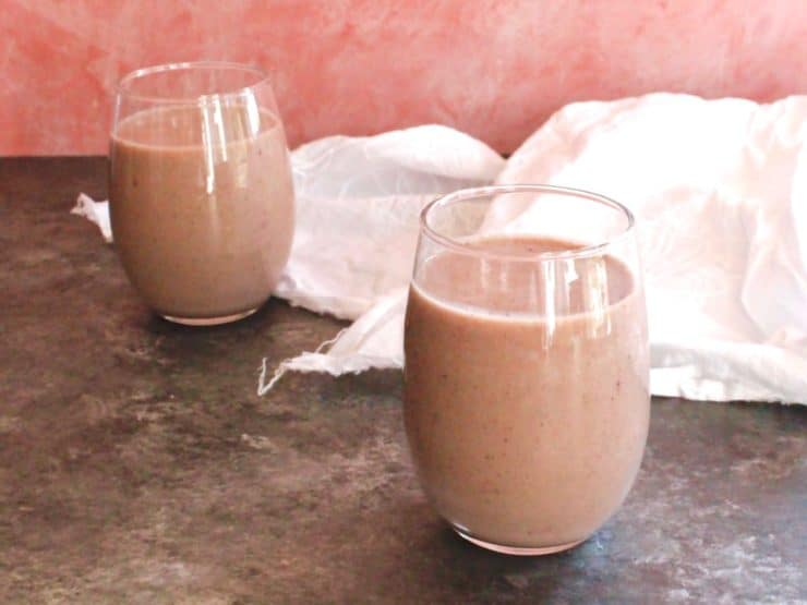 Two glasses of acai almond milk smoothie on grey concrete table with white cloth, pink wall in background.