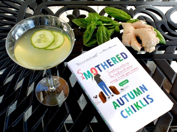 Smothered by Autumn Chiklis book on black metal table outdoors with Cucumber Ginger Martini, basil and ginger in background.