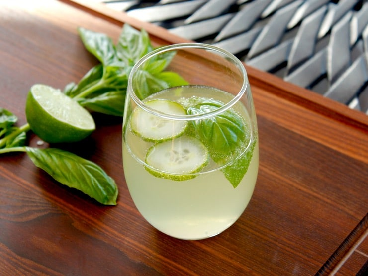 Cucumber Ginger Mocktail garnished with cucumber slices and basil on wooden cutting board on black outdoor table with basil and lime in background.