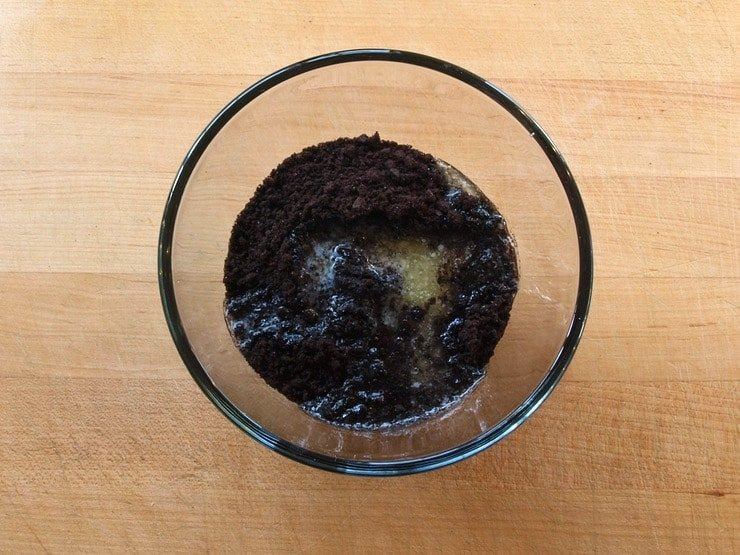Crushed chocolate cookies in a clear glass mixing bowl.