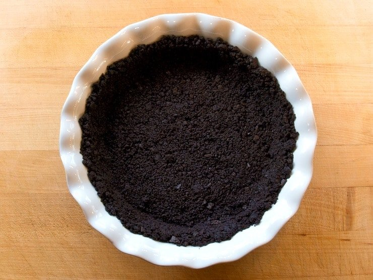 Chocolate pie crust in a white circular pie pan.