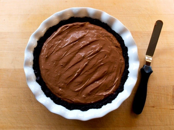 Chocolate filling inside of a chocolate crust in a white pie plate.