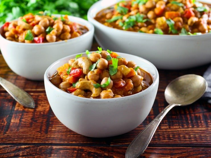 Three white bowls filled with vegan chickpea chili on a wooden table.