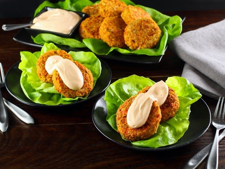 Two small dishes holding two salmon cakes topped with a spicy Sriracha sauce on a bed of lettuce. A platter of fish cakes and sauce is in the background.