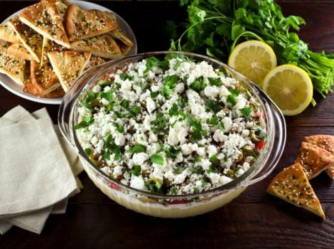 A large glass serving bowl filled with a layered dip that includes hummus, greek yogurt, Israeli salad, olives, feta cheese, and cilantro. A dish of pita chips is sitting off to the side.