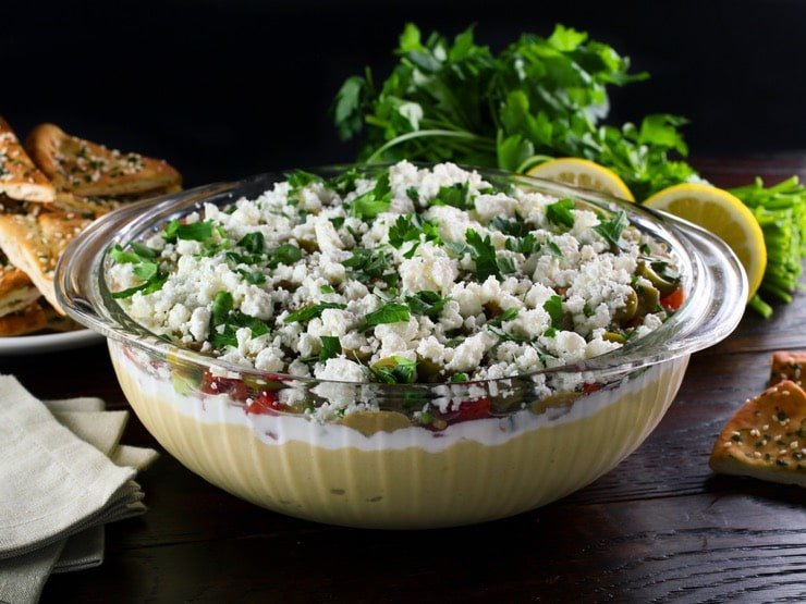 A large glass serving bowl filled with a layered dip that includes hummus, greek yogurt, Israeli salad, olives, feta cheese, and cilantro.