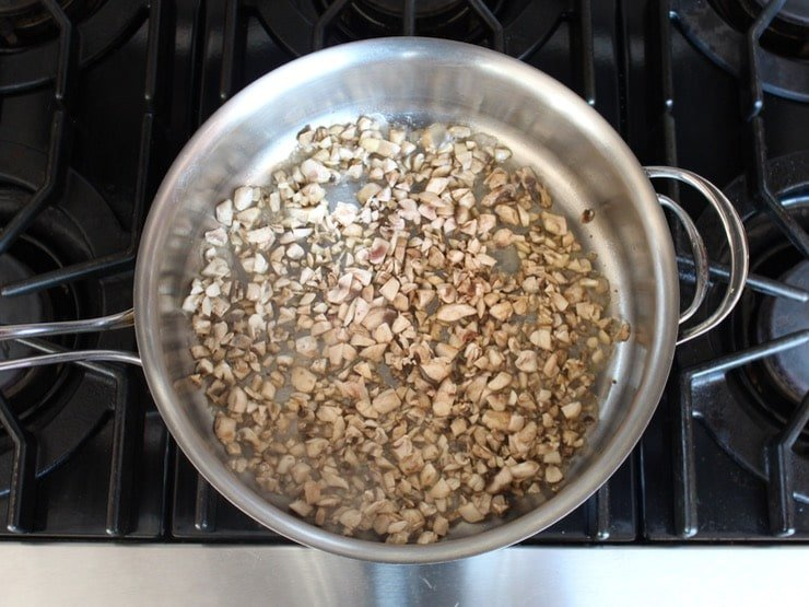 Chopped mushrooms in saute pan on stovetop.