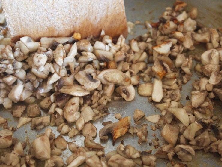Close up of chopped mushrooms in pan, searing golden brown