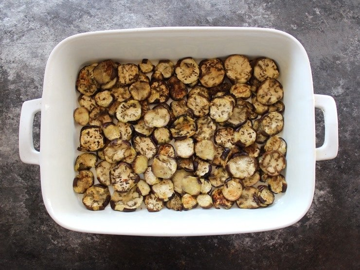 Roasted eggplant slices bottom layer in 2 quart casserole dish on concrete surface.