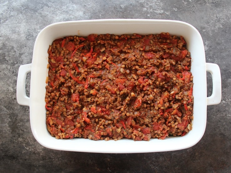 Lentil pepper and mushroom filling in 2 quart casserole dish on concrete surface.