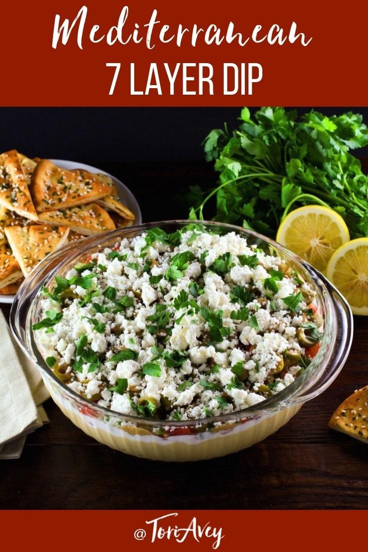 Mediterranean 7 Layer Dip - A healthy Mediterranean twist on seven layer dip with hummus, Greek yogurt, Greek olives, feta cheese and more. Serve with pita chips or crudités.   ToriAvey.com #dip #mediterranean #sevenlayerdip #hummus #greekyogurt #partyfood #healthy #TorisKitchen