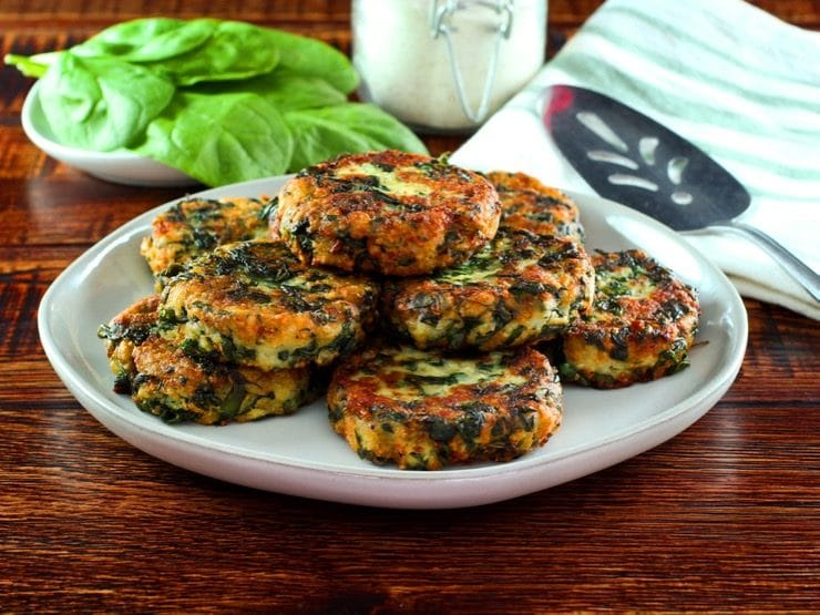 Horizontal shot - plate of fried keftes de espinaca - spinach keftes - piled on a white plate with fresh spinach, canister of breadcrumbs, spatula and cloth napkin in background.