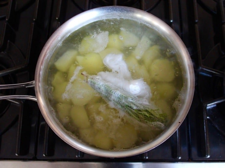 Pot of simmering potato chunks with cheesecloth bundle of rosemary floating on top on stovetop.