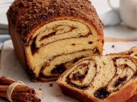 Featured - Cinnamon Babka sliced on cutting board with cinnamon stick bundle. coffee and towel in background.