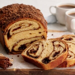 Horizontal image - Cinnamon Babka sliced on cutting board with cinnamon stick bundle. coffee and towel in background.