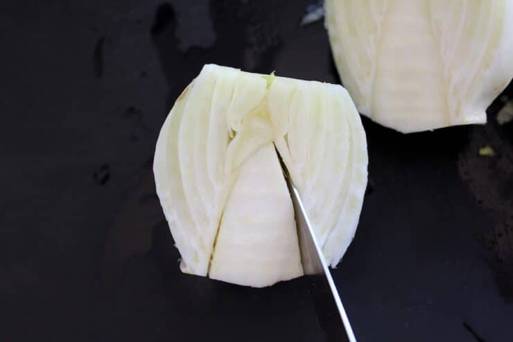 Removing the core from a half fennel bulb.