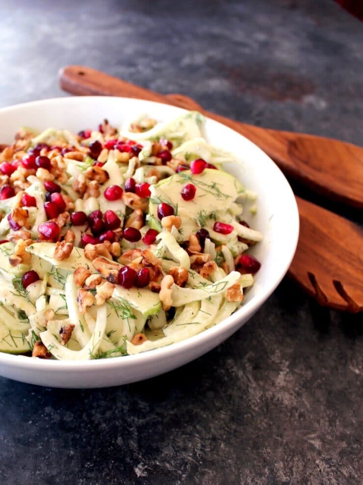 Close up of a bowl of Fennel Apple Salad with Cider Tahini Dressing, topped with pomegranate seeds, with wooden utensils.