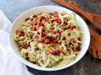 A bowl of Fennel Apple Salad with Cider Tahini Dressing, topped with pomegranate seeds, with wooden utensils and a white napkin.