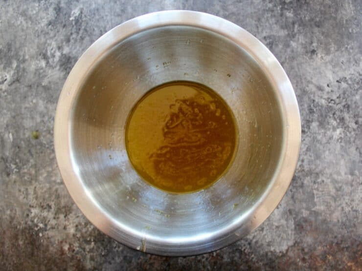 Overhead shot of lemon honey salad dressing in a metal mixing bowl.