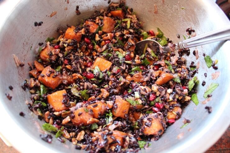 Overhead shot of black rice mixed with butternut squash, chopped fruit and fresh mint in a metal mixing bowl.