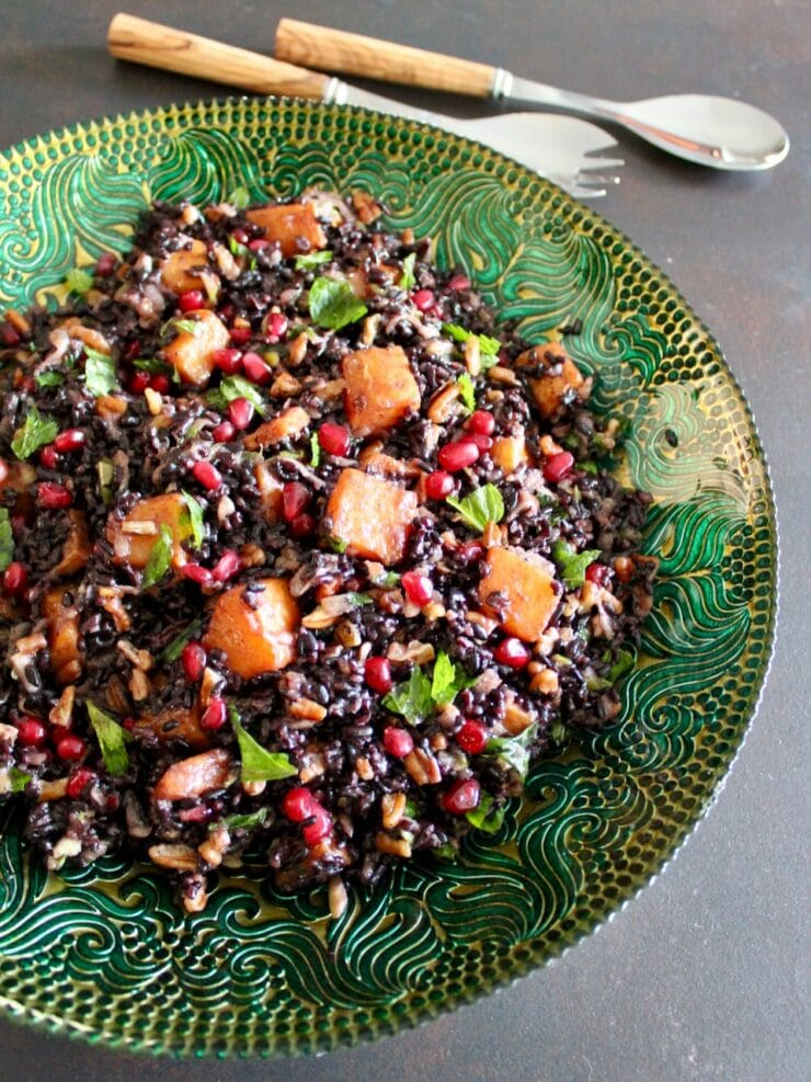 Overhead shot of black rice mixed with butternut squash, chopped fruit and fresh mint in a green decorative bowl.