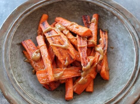 Horizontal shot of rustic tray of roasted carrots with tahini drizzle.