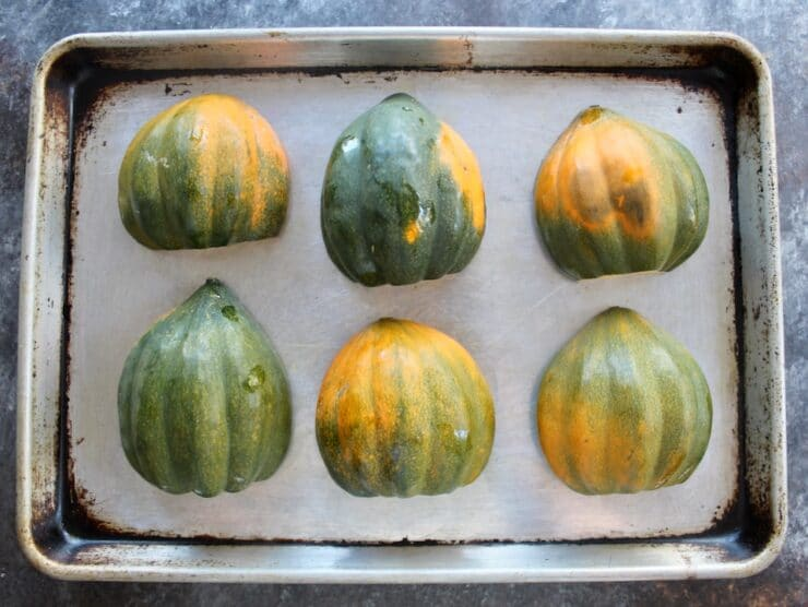 Six acorn squash halves on a baking sheet, cut side downward, skin side up