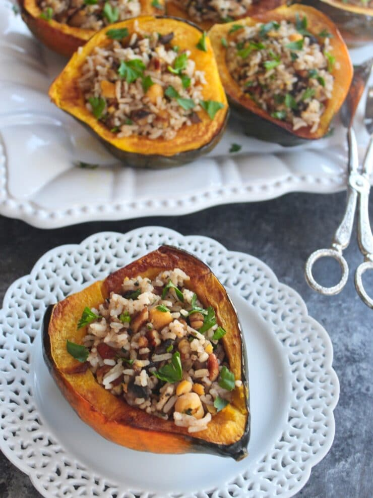 Small decorative plate with stuffed acorn squash, vegan filling - tray of stuffed squash with tongs in the background, on concrete surface
