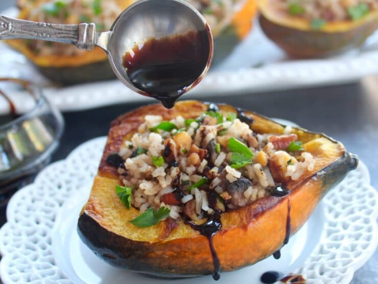 Horizontal shot of small plate with Vegan Stuffed Acorn Squash in foreground - tablespoon drizzling balsamic reduction on top, glass of balsamic reduction and tray of stuffed squash in background