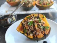 Horizontal shot of Vegan Stuffed Acorn Squash drizzled with balsamic reduction on small plate in foreground with glass of balsamic reduction and tray of stuffed squash in background
