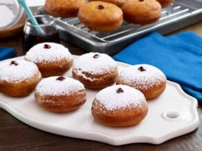 Sufganiyot on white platter dusted with sugar, more in background on cooling rack, with blue cloth towel.