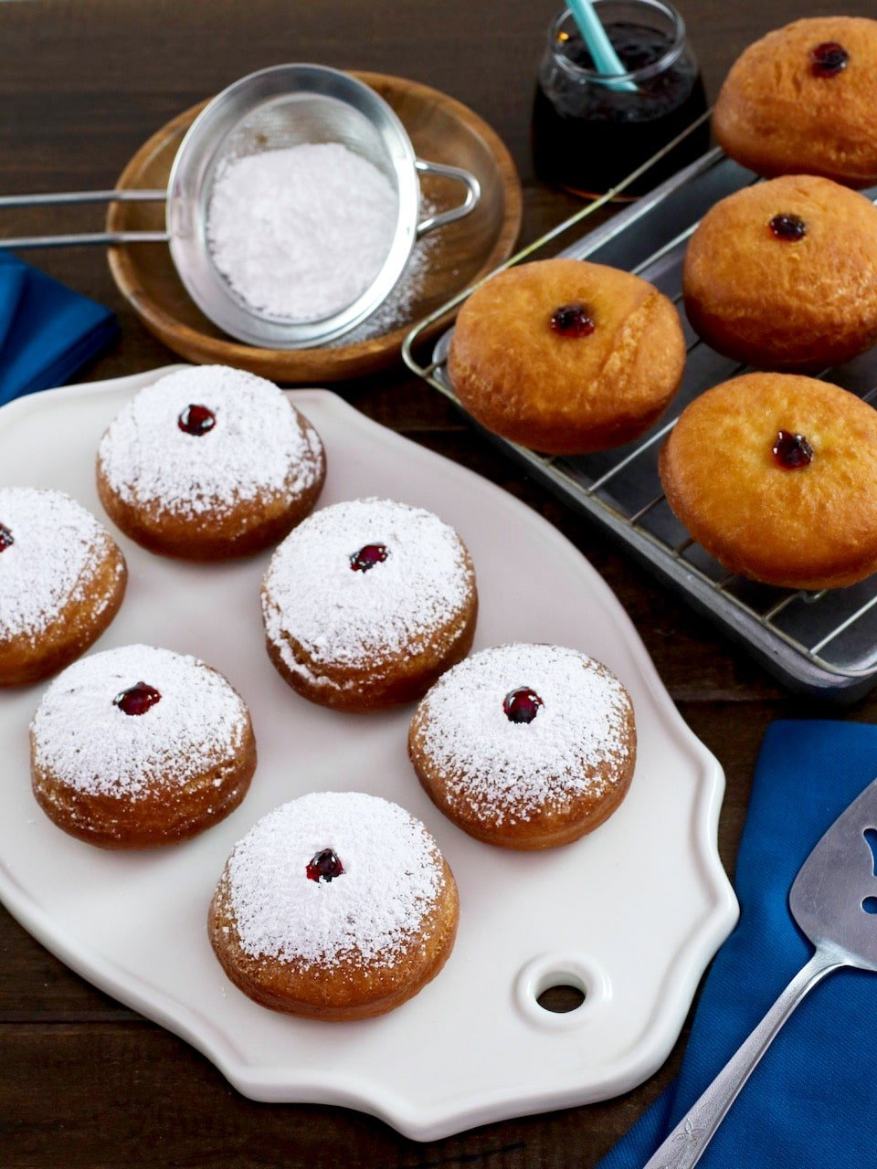 Overhead shot - sufganiyot on white platter dusted with sugar, more in background on cooling rack, with blue cloth towel. Sifter with sugar in background.