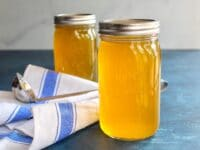 Horizontal shot of two jars of chicken stock on a blue surface with cloth napkin and soup ladling spoon.