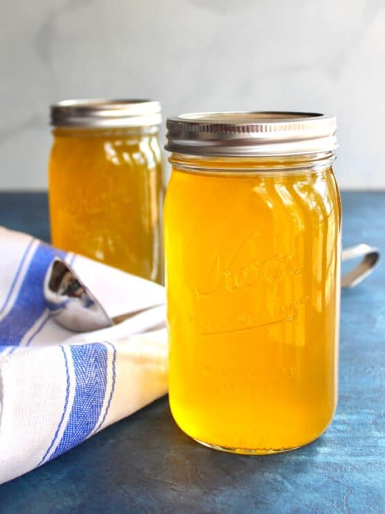 Vertical shot of two jars of chicken stock on a blue surface with cloth napkin and soup ladling spoon.