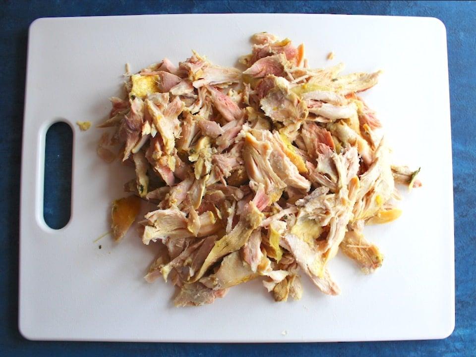 Cutting board with shredded chicken.