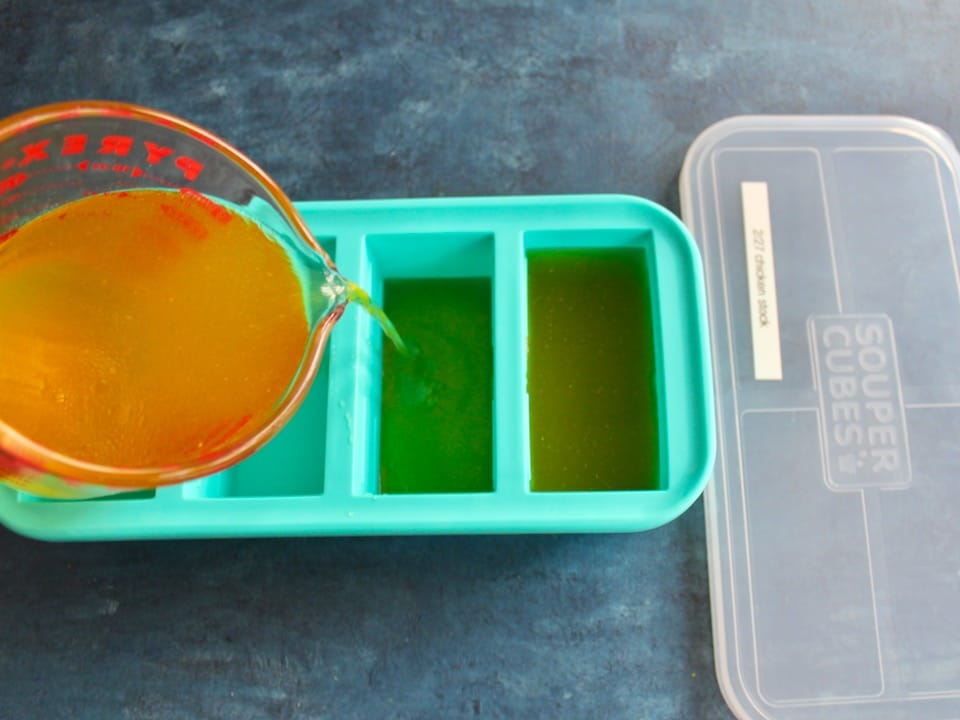 Pouring chicken stock from a measuring cup into a Souper Cubes tray with lid beside, lid labeled with date.