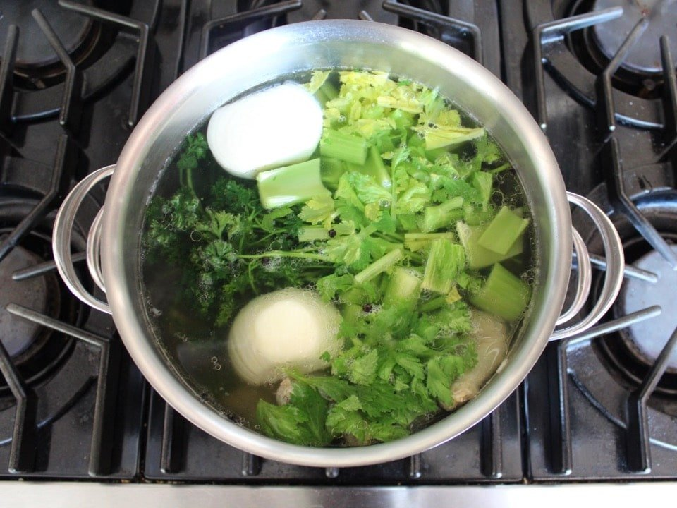 Pot full of ingredients and water for chicken stock.