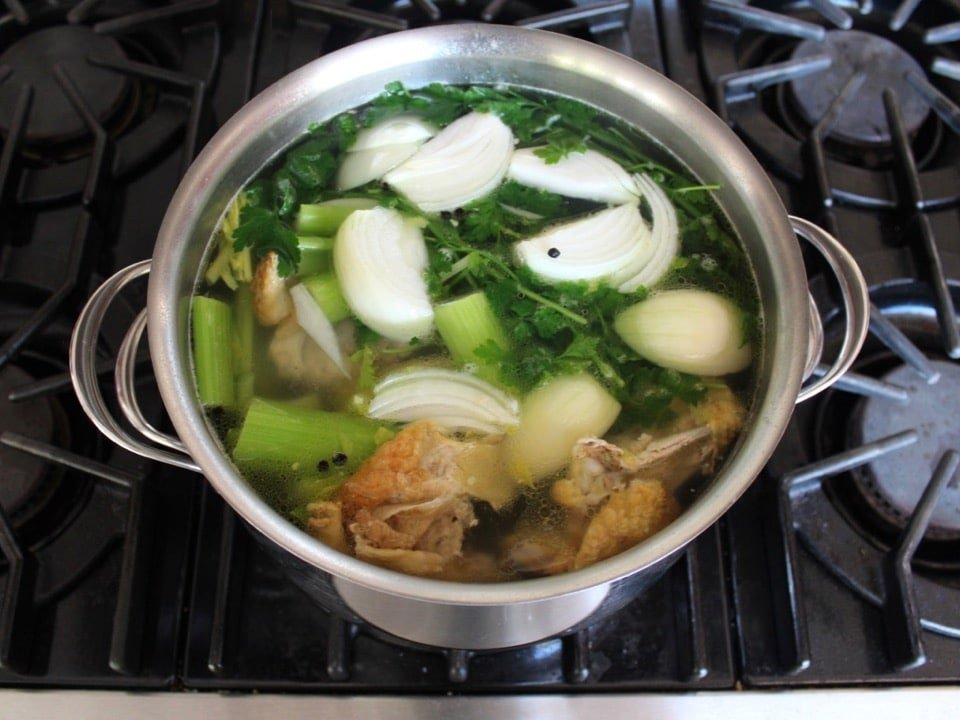 Pot of chicken stock cooking with vegetables and a roast chicken carcass.