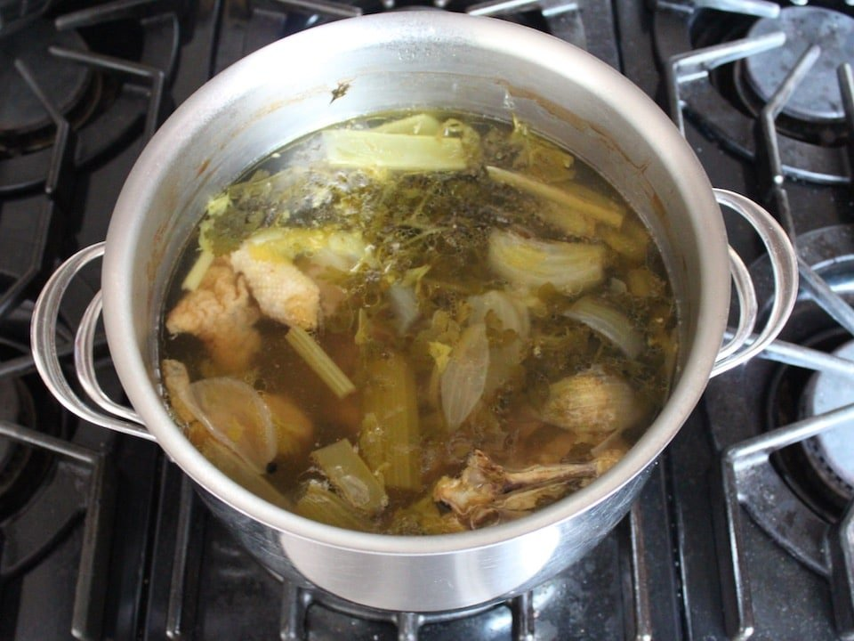 Pot of cooked chicken stock with carcass and cooked vegetables.
