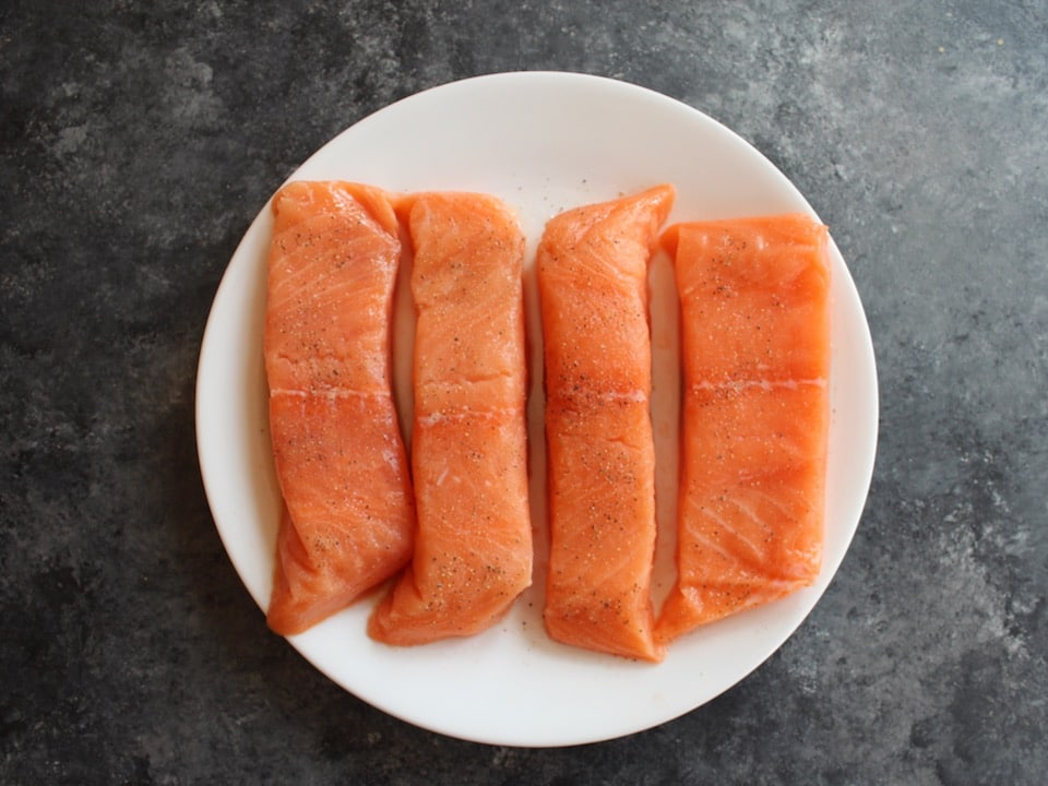Four raw salmon fillets on a white plate seasoned with salt and pepper.